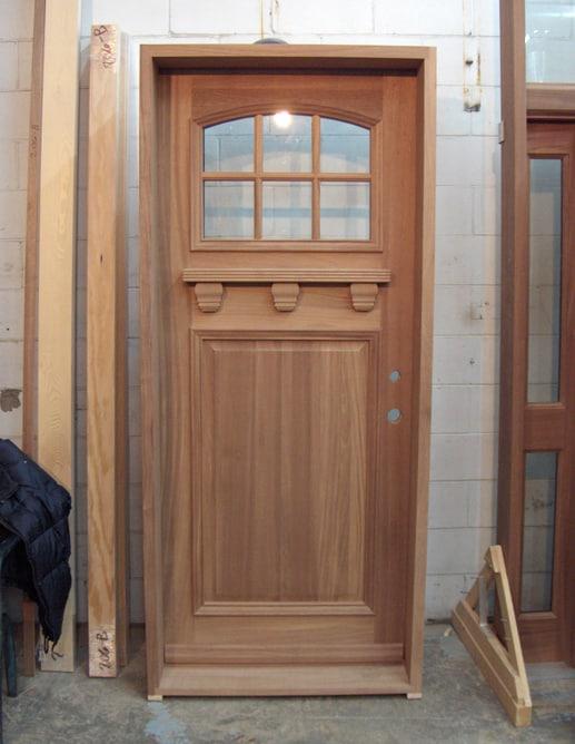 Porte extérieure en acajou avec tablette décorative.