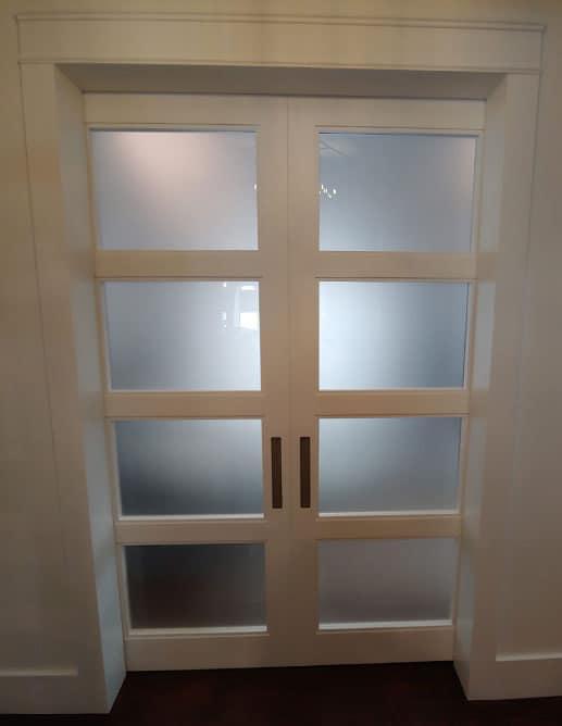 Porte coulissante de surface double camouflée par une valence en bois massif. Modèle à 4 verres acides extra clairs et avec une poignée encastrée de ±12''